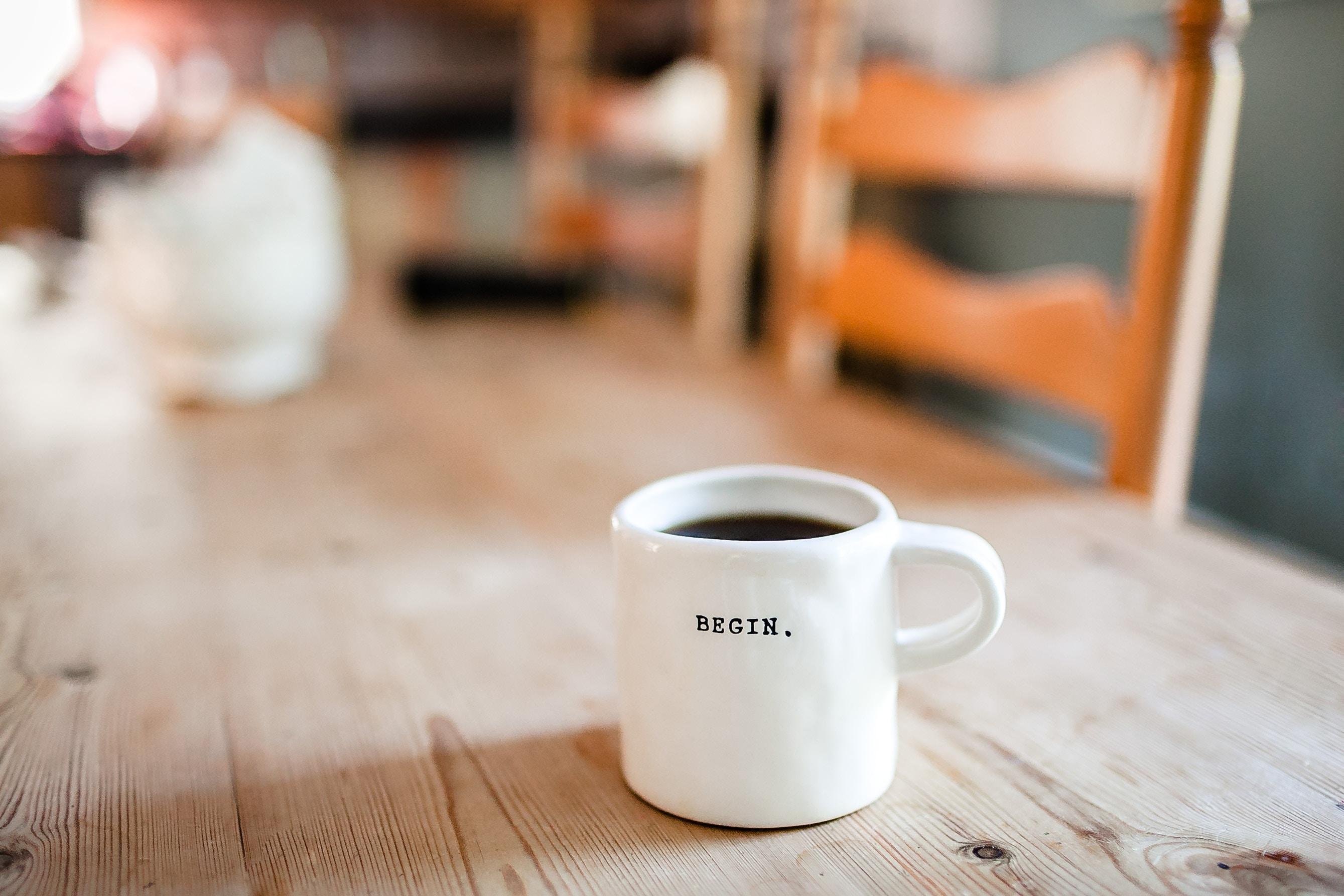 Zdjęcie kubka kawy z napisem Begin